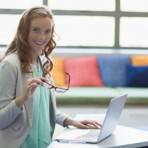 portrait-of-smiling-teacher-using-laptop-in-library